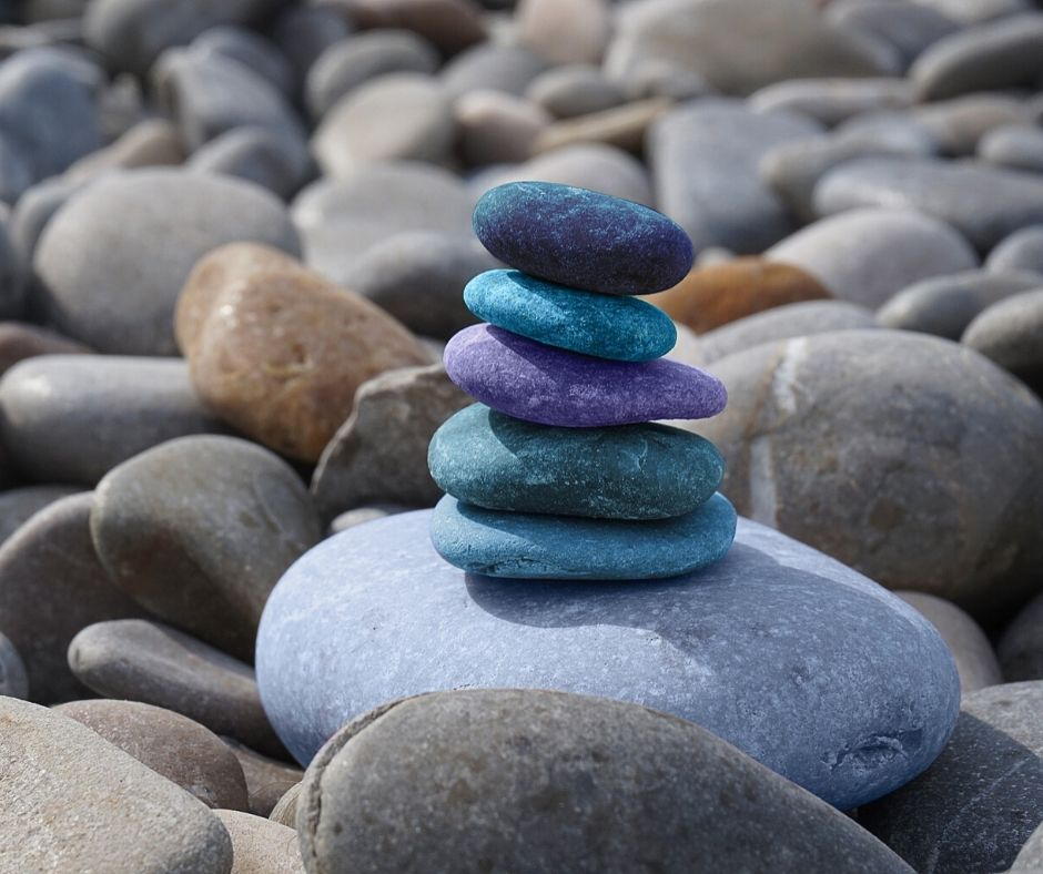 Coloured stones on a beach representing zen and feng shui